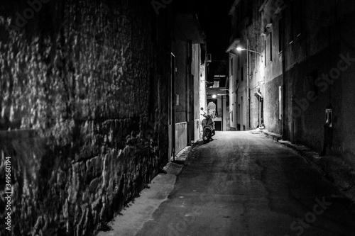 Carta da parati Empty Alley Amidst Buildings At Night