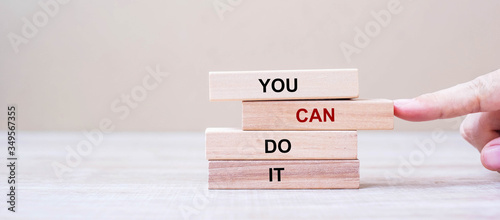 YOU CAN DO IT wooden blocks on table background, Businessman hand placing or pulling wooden block with CAN word on the tower Canvas Print