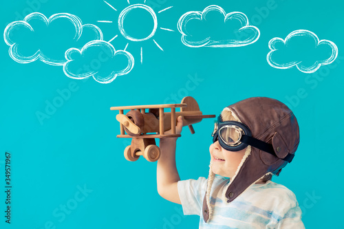 Fototapeta Happy child playing with toy wooden airplane obraz