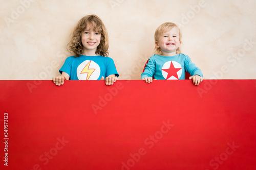 Fototapeta Superheroes children holding red banner blank obraz