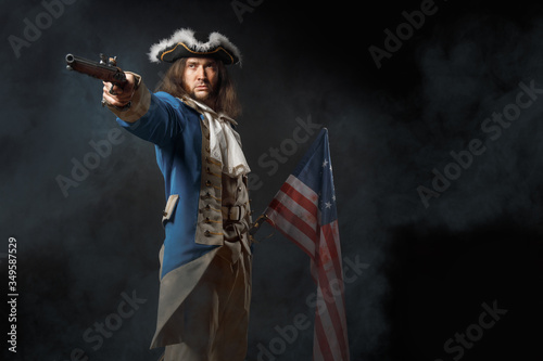 Fototapeta Man in form of officer of United States Revolutionary War with a flag and gun