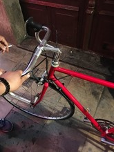 Cropped Hand Of Person Holding Red Bicycle Handle
