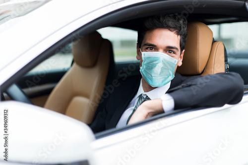 Fototapeta Handsome man driving his car wearing a mask, coronavirus concept obraz