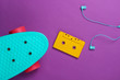 canvas print picture - Cruiser board and retro audio cassette, earphones on purple background. 80s. Top view. Minimalism.