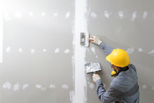 Interior Decoration Construction Furniture Builtin.Plasterer In Working Uniform Plastering The Wall Indoors.