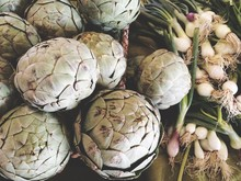 Close-up Of Globe Artichoke And Green Onions On Table