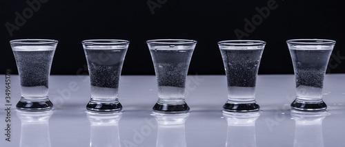 Fototapeta Glasses with vodka on a white table on a black background obraz na płótnie