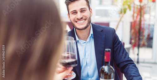 Man and woman enjoying a glass of red wine with their meal