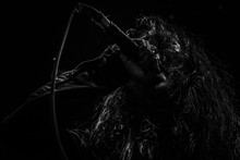 Singer With Long Hair Holding Microphone While Singing Against Black Background