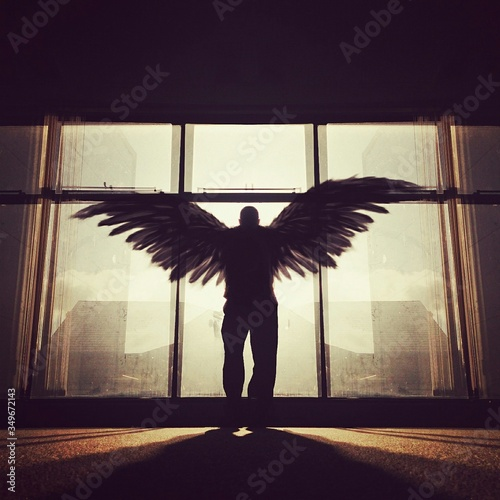 Leinwand Poster Silhouette Man With Wings Standing In Front Of Window