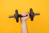 Working out concept. Cropped photo of a strong man holding dumbbell in hand isolated on yellow background