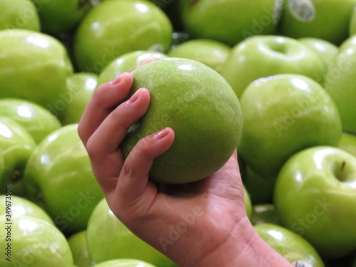 Photographie Cropped Hand Of Person Holding Granny Smith Apple
