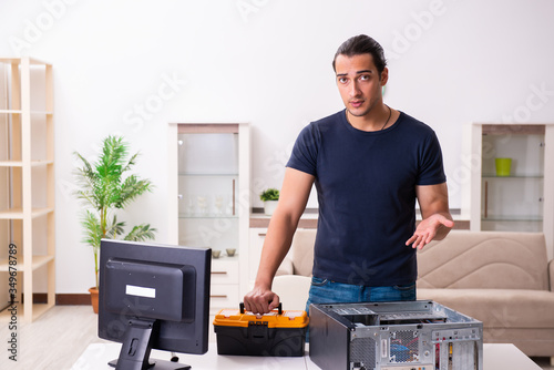 Fototapety, obrazy: Young man repairing computer at home
