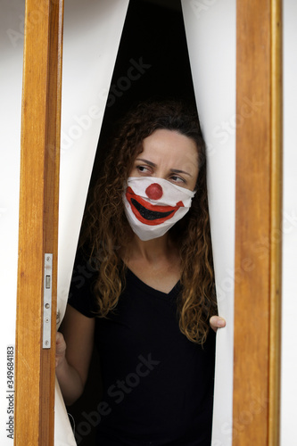 Woman with protective mask painted as a clown in São Paulo, with the feeling of having been deceived Fototapeta