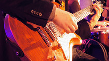 Midsection Of Man Playing Electric Guitar During Music Concert
