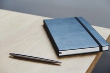 Close-up Of Pen And Diary On Table
