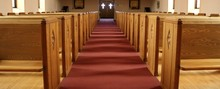 Looking Down Long Aisle Toward The Front Doors With Light Coming Through The Glass Crosses In Empty Church