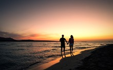 Couple Walking At Beach Against Sky During Sunset