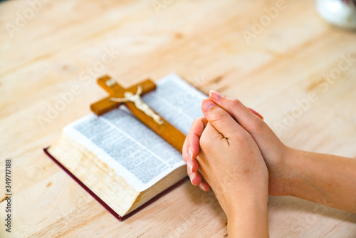 Obraz Cropped Hands Of Woman Praying By Bible And Cross On Table - fototapety do salonu