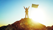 Rear View Of Man With Arms Raised Standing By Flag On Rock Against Sky
