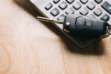 High Angle View Of Calculator And Car Key On Table