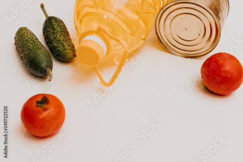 Fototapeta cucumbers, tomatoes, vegetable oil, eggs and canned goods isolated on white background.Food supplies crisis food stock for quarantine.Food delivery, Donation, coronavirus.Tape measure. obraz na płótnie