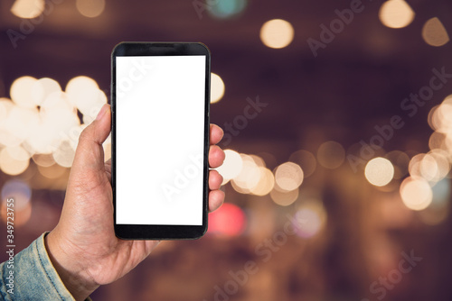 Foto Cropped Hand Of Man Using Smart Phone In Illuminated City At Night