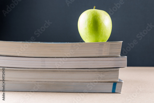 Photographie Close-up Of Books With Granny Smith Apple On Table