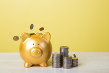 Coins With Piggy Bank Against Yellow Background On Table