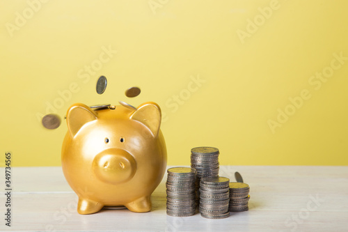 Fotografija Coins With Piggy Bank Against Yellow Background On Table