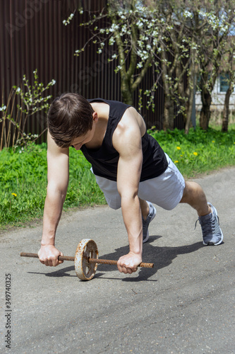 Photo A young man is engaged in fitness on a makeshift simulator of an iron wheel and