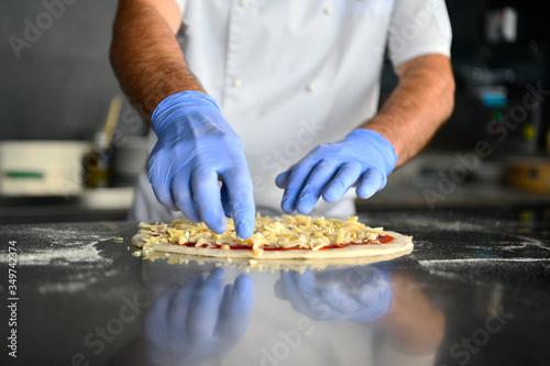 Obraz chef  with protective coronavirus face mask preparing pizza - fototapety do salonu