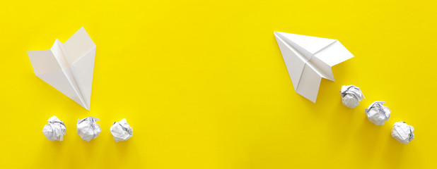concept image of crisis and opportunity . one paper plane taking off while the second is crashing. yellow background