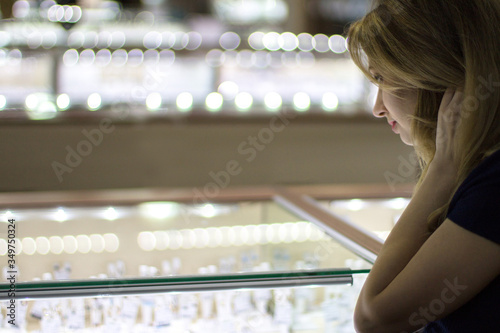 Fényképezés Girl looks at jewelry in jewelry store bijouterie