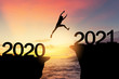 canvas print picture - Silhouette man jumping between cliff with number 2020 to 2021 at tropical sunset beach. Freedom challenge and travel adventure holiday concept.