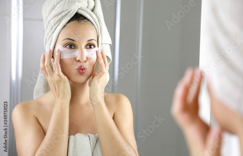 Photo Beautiful woman applying anti-fatigue under-eye mask kissing herself in the mirror in the bathroom