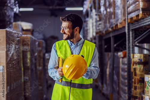 Young smiling supervisor in vest, helmet in his hands and folder under armpit going around warehouse and checking on inventory Wallpaper Mural