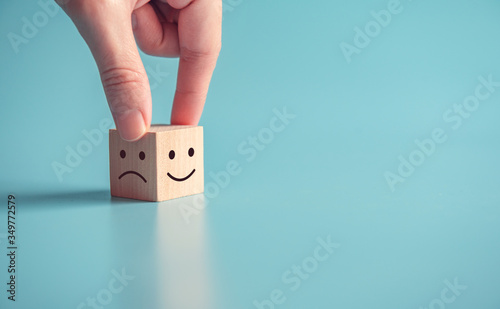 Obraz na plátně Close up customer hand choose smiley face and sad face icon on wood cube, Service rating, satisfaction concept, copy space