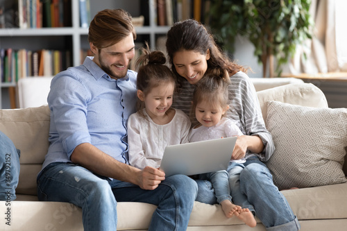 Happy young Caucasian family with small daughters relax on couch at home watching funny video on laptop, smiling parents with little girls children enjoy home weekend using computer gadget together