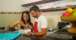 young beautiful and happy mixed ethnicity couple in love cooking together at home kitchen the caucasian husband in red apron and his Asian wife helping him and enjoying cheerful