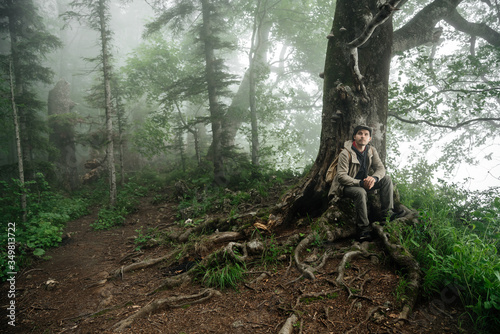 Fototapeta man in a hiking suit is resting near an old lonely tree in a foggy forest. Hiking, travel and outdoor recreation. obraz