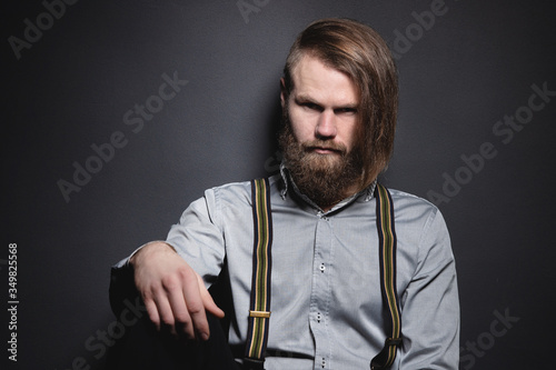 Fotografie, Tablou Contrasting low key portrait of a bearded long-haired stylish brutal man in a gray shirt with suspenders sternly looks at the camera