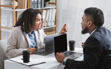 Annoyed Black Woman Quarelling With Her Coworker At Workplace, Empty Space