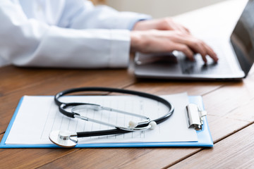 Online answers to patient questions. Hands of woman doctor typing on laptop