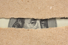 One Hundred Dollar Bill Behind Brown Craft Ripped Paper