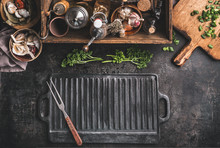Grill Or BBQ Food Background With Empty Cast Iron Grill Griddle And Meat Fork  On Roast Rustic Kitchen Table. Wooden Box With Seasonings, Oils And Other Kitchen Utensils.Top View. Place For Design