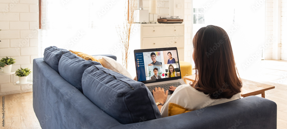 Fototapeta Young Asian businesswoman work at home and virtual video conference meeting with colleagues business people, online working, video call due to social distancing at home office