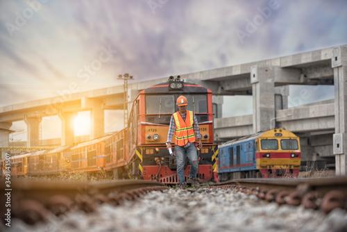 Foto worker on railways with  locomotive  on background.