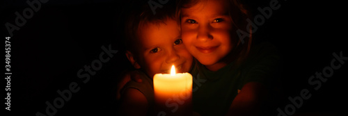 Fototapeta happy kids siblings boy and girl admires a burning wax candle in the evening at home. banner obraz
