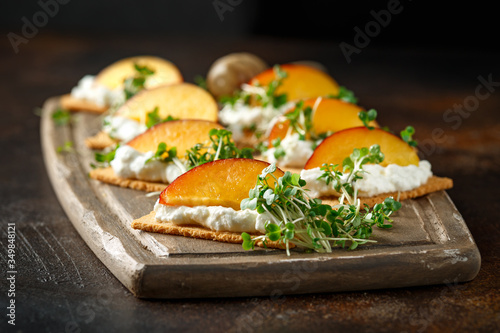 Obraz na plátně Cottage cheese and nectarine wedges on melba toast appetizers drizzled with runny honey and served with cress salad microgreen